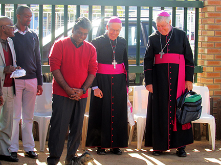 Fr Shiju regards a new pet cat with leaders of the Chicago Catholic Church