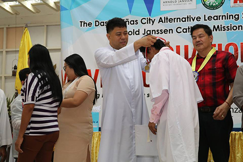 Fr. Jerome Marquez, SVD places a medal on a recent graduate of the Arnold Janssen Mission Foundation