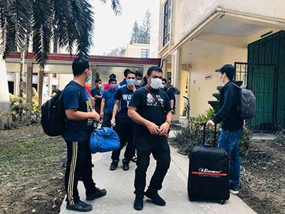 young people wearing protective masks while moving out of dorm