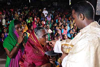 Fr. Francis Rayappan, SVD, distributes Holy Communion during his first Mass in India