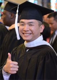 Hoang Tran gives a thumbs up at his graduation ceremony